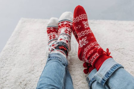 cropped image couple sitting on carpet in jeans and christmas socks