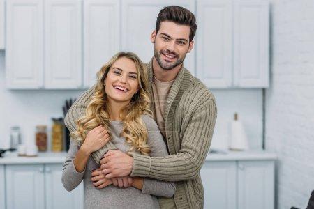 smiling handsome boyfriend hugging attractive girlfriend in kitchen and they looking at camera