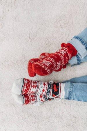 Photo for Cropped image couple sitting on carpet in jeans and red christmas socks - Royalty Free Image