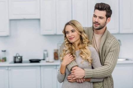 Photo for Handsome boyfriend hugging attractive girlfriend in kitchen and they looking away - Royalty Free Image