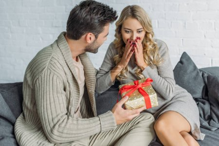 handsome young man presenting gift for surprised girlfriend at home