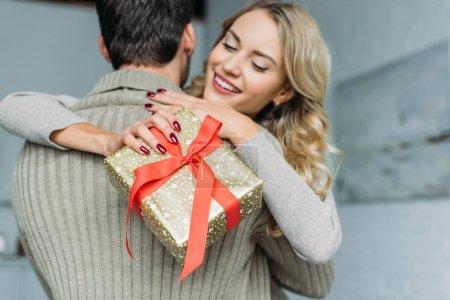 Photo pour Belle jeune femme avec boîte cadeau embrassant son petit ami à la maison - image libre de droit