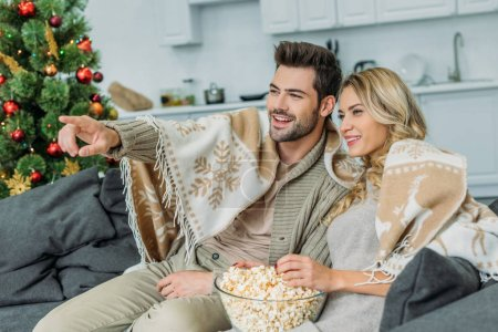 happy young couple with popcorn watching movie at home