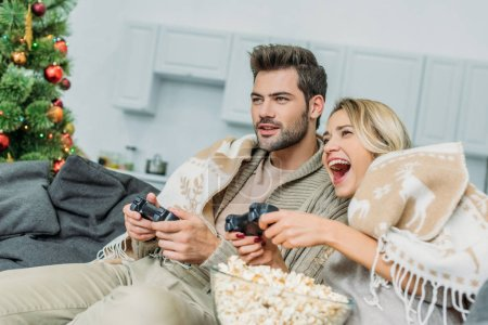 happy young couple with popcorn playing video games together on couch at home
