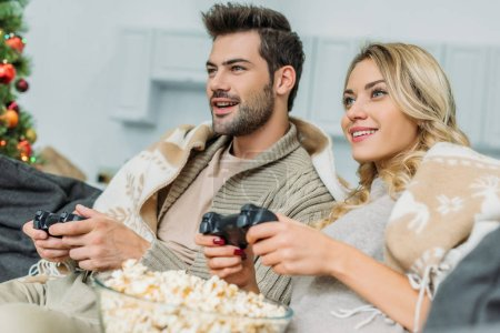beautiful young couple with popcorn playing video games together on couch at home