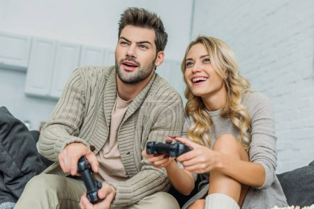 smiling young couple playing video games together on couch at home