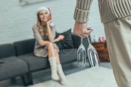 cropped shot of man with champagne glasses standing in front of woman in santa hat sitting on couch at home