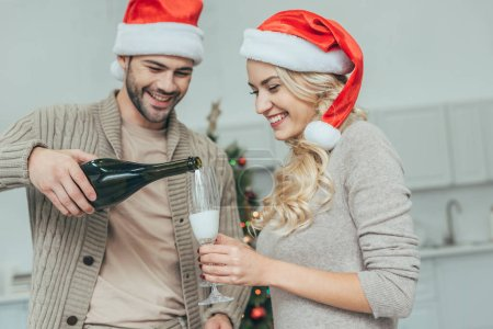 happy young couple pouring champagne into glasses in front of christmas tree at home