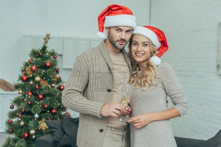 happy young couple with champagne glasses looking at camera in front of christmas tree at home