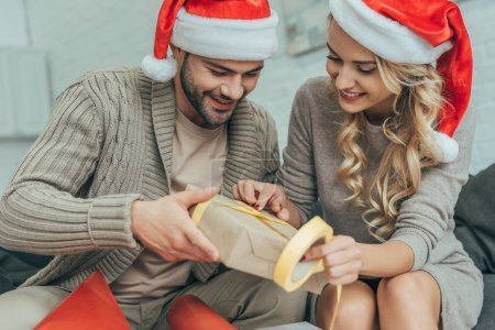 creative young couple in santa hats decorating christmas gift together at home