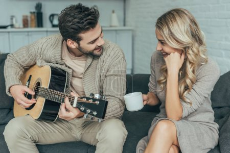 happy young man playing guitar for girlfriend at home while she sitting on couch with coffee