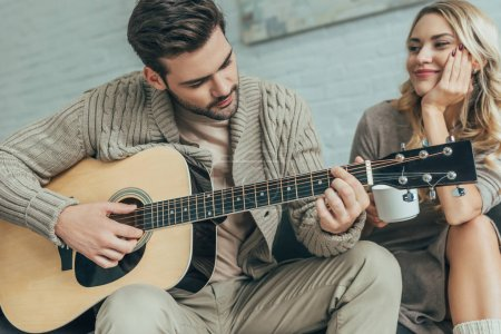handsome young man playing guitar for girlfriend at home while she sitting on couch with coffee
