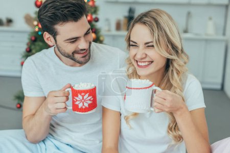 laughing young couple with cups of cocoa sitting in bed at home on christmas