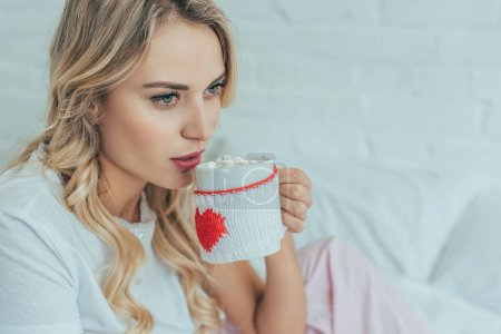 beautiful young woman drinking cocoa with marshmallow in bed at home
