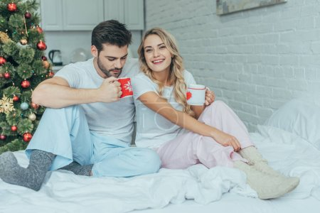 happy young couple with cups of cocoa sitting in bed at home on christmas