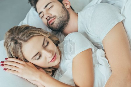 close-up shot of beautiful young couple sleeping together in bed at home