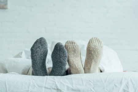 cropped shot of couple in woolen socks lying in bed at home