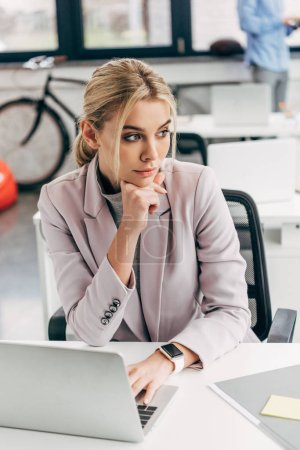 pensive young businesswoman looking away while working with laptop in office