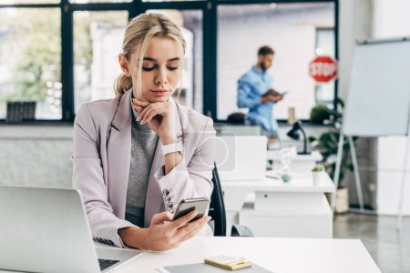 beautiful young businesswoman using smartphone at workplace