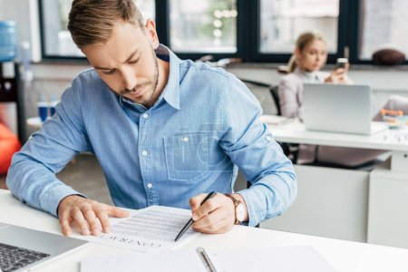 young businessman working with contract in office