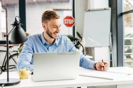 Photo pour Sourire de jeune homme d'affaires avec ordinateur portable et de prendre des notes au milieu de travail - image libre de droit