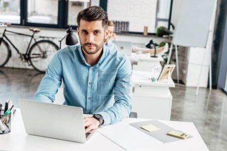 Photo pour Beau jeune homme d'affaires avec ordinateur portable et regardant la caméra dans le Bureau - image libre de droit