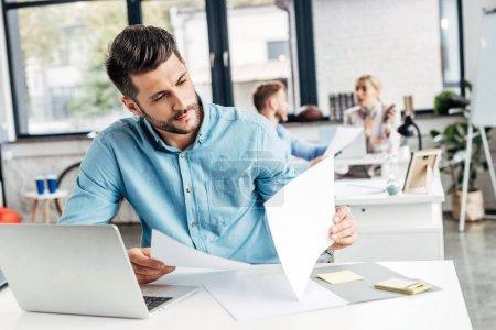 Photo pour Concentré jeune homme d'affaires travaillant avec des papiers et un ordinateur portable dans le bureau - image libre de droit