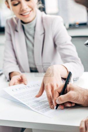 Photo pour Plan recadré d'une femme d'affaires souriante détenant un contrat et un homme d'affaires le signant en fonction - image libre de droit