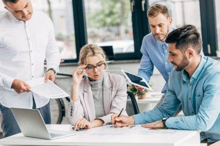 Photo pour Jeune femme d'affaires en lunettes travaillant avec des collègues masculins au bureau - image libre de droit