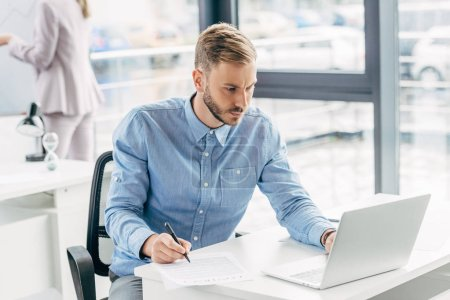 focused young businessman using laptop and taking notes at workplace
