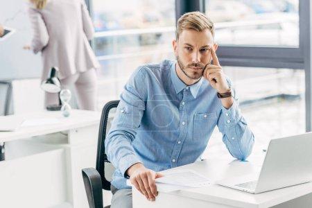 Photo pour Gentil jeune homme d'affaires assis à table avec ordinateur portable au bureau - image libre de droit