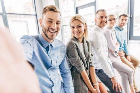 Photo pour Foyer sélectif de joyeux jeune start-up équipe souriant à la caméra dans le bureau - image libre de droit