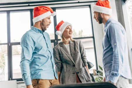 young start up team in santa hats looking at each other in office