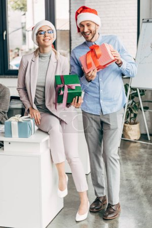 happy businessman and businesswoman in santa hats holding gift boxes and smiling at camera in office