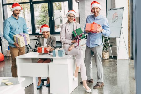 happy young start up team in santa hats holding christmas presents at workplace
