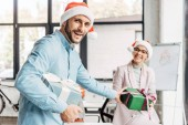 happy young businessman presenting christmas gift to female colleague in office