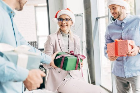 smiling young coworkers presenting christmas gifts in office