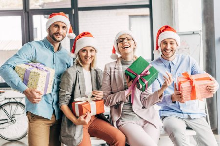 Photo for Happy coworkers in santa hats holding presents and smiling at camera in office - Royalty Free Image
