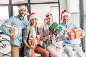 happy coworkers in santa hats holding presents and smiling at camera in office