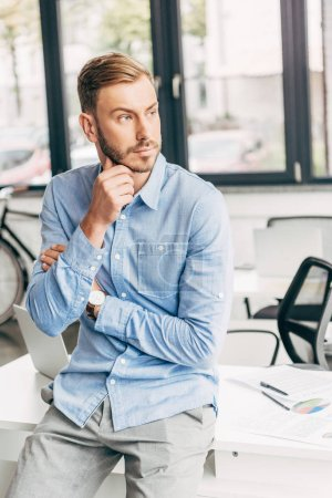Photo for Thoughtful young businessman with hand on chin sitting on table and looking away in office - Royalty Free Image