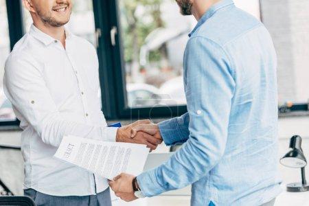 Photo pour Recadrée tir des hommes d'affaires souriants tenant du contrat et se serrant la main au bureau - image libre de droit