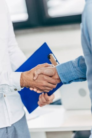cropped shot of colleagues shaking hands during business meeting