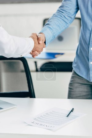 cropped shot of businessmen shaking hands above table with contract