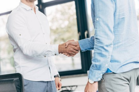 cropped shot of businessmen shaking hands in office