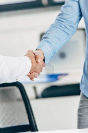 Photo pour Gros plan vue partielle des hommes d'affaires se serrant la main au milieu de travail - image libre de droit