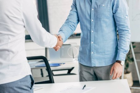 Photo for Cropped shot of businessmen shaking hands at workplace - Royalty Free Image