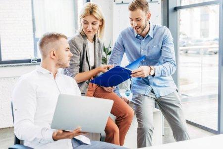 junges Business-Team arbeitet mit Laptop und Papieren im Büro
