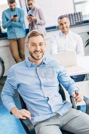 Foto de Joven hombre de negocios guapo sonriendo a la cámara mientras trabaja con colegas en la oficina - Imagen libre de derechos