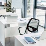 laptop on tables in empty modern office