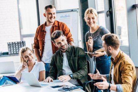 Photo pour Groupe de jeunes entrepreneurs travaillant avec des ordinateurs portables et de bavarder ensemble au bureau - image libre de droit